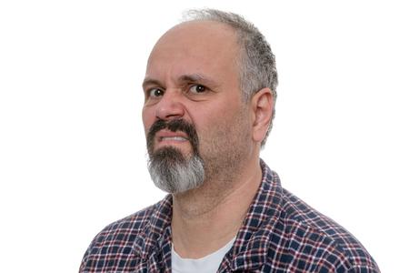 desprecio: hombre calvo enojado con barba se burla de la cámara mientras llevaba camisa a cuadros Foto de archivo