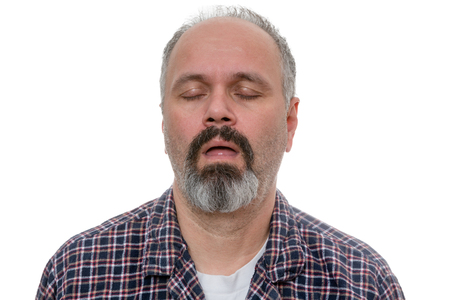 somnolent: Sleepy man with beard and plaid shirt snores with his eyes closed against a white background