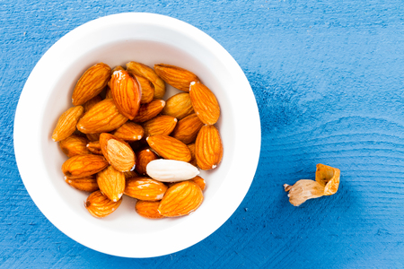 Bowl of fresh raw almonds with one peeled against a blue background as seen from an overhead view