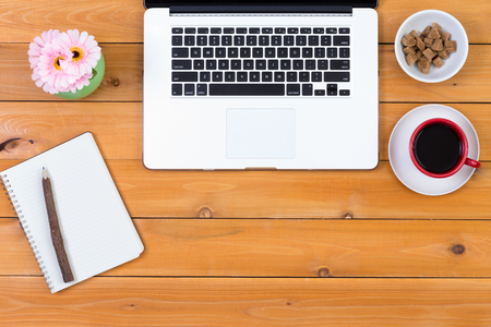 energising: Neat clean wooden desk with laptop computer, notepad, flowers and a mug of black espresso coffee with sugar cubes, overhead view with copy space Stock Photo