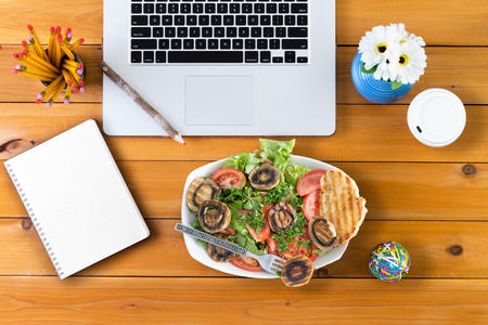 Overhead view of lunch break at the neatly organized desk along with computer and salad Stock Photo