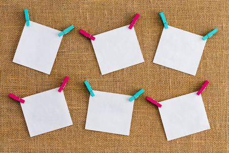 Six misaligned blank white notepads on hessian or burlap fabric hanging from alternating colorful pink and blue clothespins in a concept of organisation and business planning