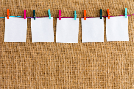 clothespegs: Neat row of hanging blank white notepads suspended by clothespins from cotton forming a top border over burlap or hessian textile with weave texture and copy space Stock Photo