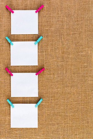 clothespegs: Side border of neatly hanging blank white square notepads on colorful wooden clothespins over a rustic hessian or burlap textile background with copyspace, vertical format