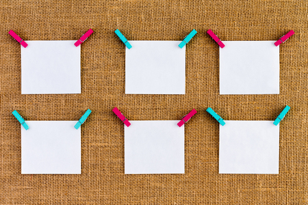 Six neatly aligned blank white notepads suspended from alternating blue and pink wooden clothespins over rustic burlap or hessian woven fabric