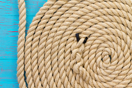 Thick rope in wound up in spiral shape over cracked wooden board background with copy space