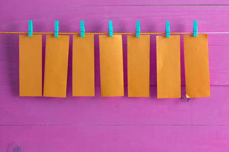 identical: Blank orange note pad sheets hanging from string over painted purple wooden background