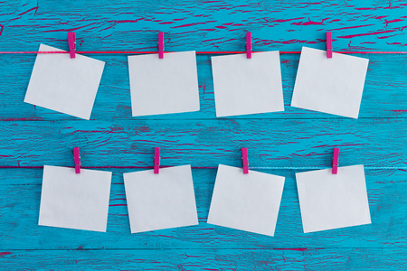 Eight blank white memo pads hanging from colorful wooden pink clothes pegs over an exotic turquoise blue crackle paint wooden panel in a concept of planning, agenda and organisation