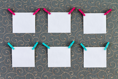 jot: Six square item or note paper tags with clothespins attached on top corners over cotton thread gray background