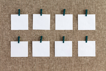 Precisely aligned rows of blank memo pads hanging from wooden clothes pegs over a textured woven burlap background in a concept of organization Stock Photo