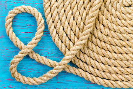 And symbol formed from a loop in a new neatly coiled round rope over a crackle paint wooden blue background in a close up view showing the detail of the natural fibers Stock Photo