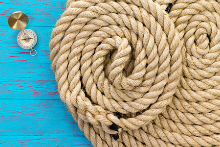 Two neatly coiled ropes and a magnetic compass over a colorful crackle paint blue background in a concept of marine rigging, boating, mountaineering, voyage, exploring and adventure