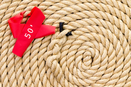 New strong rope with red 50 foot marker and central knot for a tug of war challenge or competition coiled neatly in a spiral in a full frame view