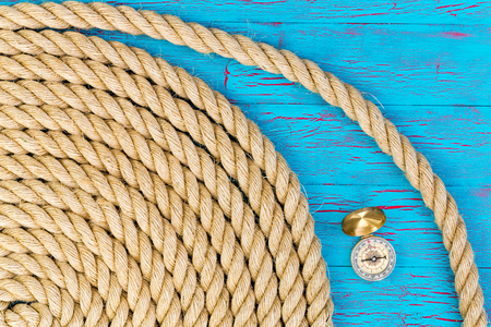 seafaring: Carefully wound rope with compass over blue for theme about boating or maritime industries Stock Photo