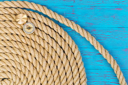 Thick rope and open directional compass over blue painted wooden background with copy space Imagens