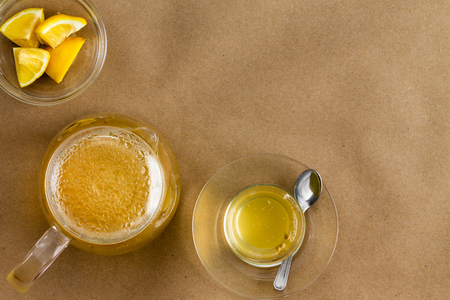 top angle: Top down view on full serving of linden tea, lemon and glass cup with copy space over brown background Stock Photo