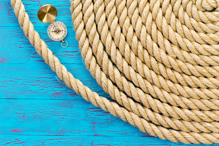 coiled rope: Neatly wound and coiled natural fiber rope with an open magnetic compass on a blue crackle paint wood background conceptual of nautical and marine themes and navigation, with copy space Stock Photo