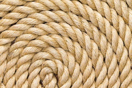 Rope background texture neatly wound into a coil showing the detail of the natural jute, sisal or hemp fibers in a full frame view Stock Photo