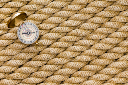 Small magnetic compass on diagonal strands of a new natural fiber rope conceptual of nautical navigation and shipping or of terrestrial exploration and mountain climbing in a full frame background Stock Photo