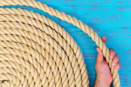 coiled rope: Close up background shot of the hand of a man or mariner holding a loop of a neatly coiled new rope over a turquoise blue crackle paint wooden panel in a conceptual image