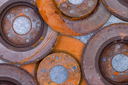 corrosion: Layer of overlapping old rusty brake rotors with advanced corrosion and oxidation of the metal in a full frame background texture