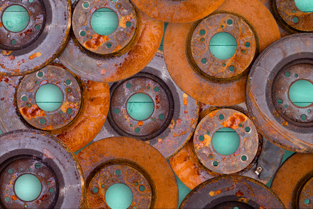 consumable: Conceptual image of overlaid old weathered rusty and corroded brake rotors from a motor car in a full frame view on a green wooden table background