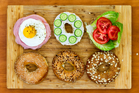 accompaniment: Tasty bagels prepared for a picnic neatly sliced and arranged on a wooden cutting board with fired egg and ham, cucumber and cheese and lettuce and tomato salad fillings