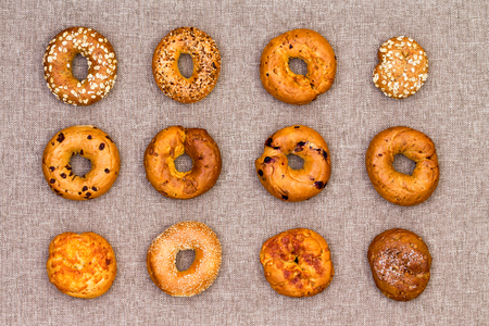 Twelve different speciality bagels displayed on a neutral beige cotton fabric background arranged in neat rows viewed from above for advertising or marketing