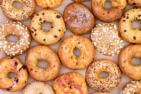 Assorted variety of different flavored freshly baked bagels in a full frame background on burlap viewed from above in an abstract pattern Reklamní fotografie - 65788141