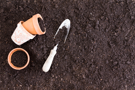 Three small clay pots beside spade in dirt as seen from an overhead view