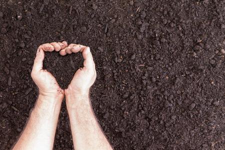 Un par de manos que sostienen el suelo en forma de corazón sobre un terreno descubierto, con copia espacio para el concepto sobre los hobbies y el amor por la jardinería
