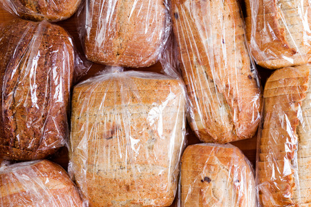 Assortment of different healthy white, wholegrain and wholewheat sliced loaves of fresh bread sealed in plastic bags ready to be distributed in a food drive, full frame overhead view