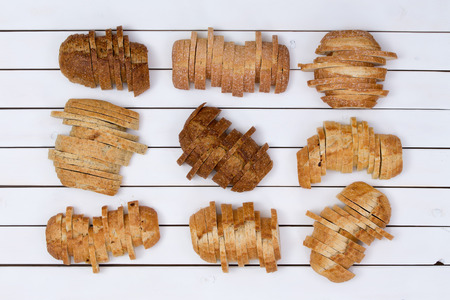 staggered: Top down view on nine sliced loaves of various wheat and white flour breads over white panel background