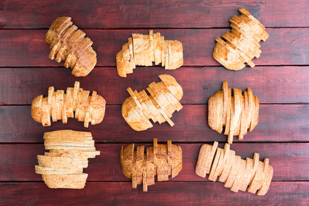 staggered: Top down view on nine sliced loaves of speciality wheat and white flour breads in staggered formation on dark stained wooden background