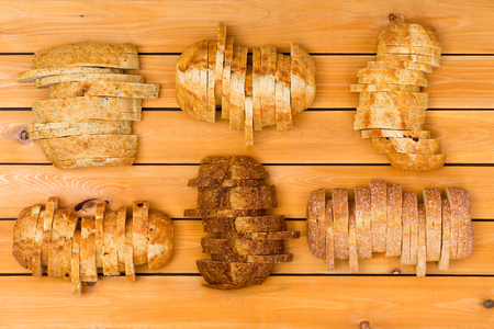 staggered: Top down view on six sliced loaves of various wheat and white flour breads in staggered formation on wooden background