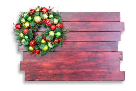 staggered: Colorful traditional Christmas wreath hanging in the corner on mahogany stained staggered wooden boards with copy space on a white background Stock Photo