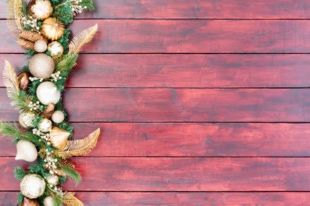 caoba: Elegante borde blanco y oro con una variedad de adornos para árboles entrelazados con follaje perenne y las bayas al lado en caoba manchada tablas de madera con espacio de copia Foto de archivo