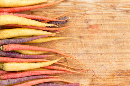 ingredients tap: Border of colorful varieties of whole raw fresh carrots arranged to the side of a cutting board with copy space ready to be prepared for cooking