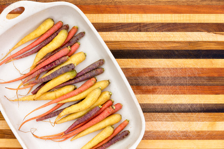 Multicolored colorful fresh whole raw carrots on a platter over a decorative striped wooden cutting board in complimentary colors with copy space