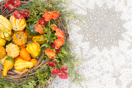 variegated: Colorful autumn centerpiece with ornamental gourds or squashes and matching orange flowers and fresh green foliage in a wicker wreath viewed from above on a Thanksgiving table Stock Photo