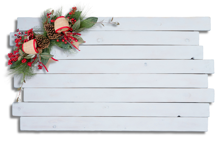 Rustic elegant Christmas decoration with green foliage, pine cones, red berries and ribbon arranged in the corner on white wood boards arranged in an offset pattern with copy space