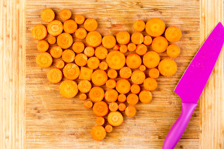 Top down view on various sized chopped raw orange colored carrots arranged in heart shape beside purple knife on wooden cutting board