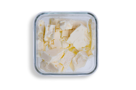 Dish of small portions of full cream feta cheese made from cow milk ready to be served at table, overhead view on white