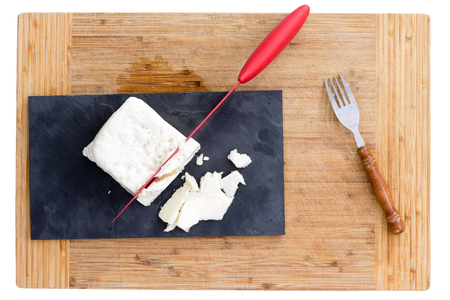 Top down view of red knife cutting white feta cheese on purple paper and fine wooden cutting board. Includes fork. Archivio Fotografico