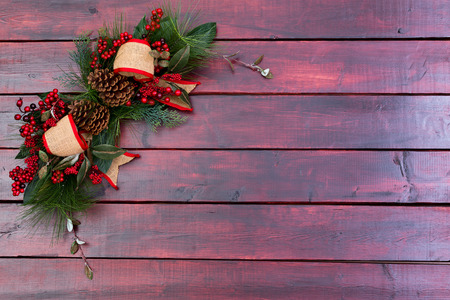 Rustic Christmas background with a simple stylish decoration of green leaves, red berries, cones and burlap ribbon on mahogany stained wooden boards with copy space for your seasonal greeting