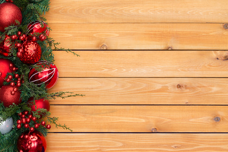 garlands: Colorful red Christmas garland border with tree ornaments and berries in evergreen foliage arranged to the side on cedar wood boards with copy space Stock Photo