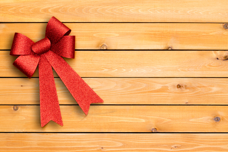 Stylish festive red Christmas ribbon arranged neatly in the corner of a cedar wood board background with copy space on decorative woodgrain and knots