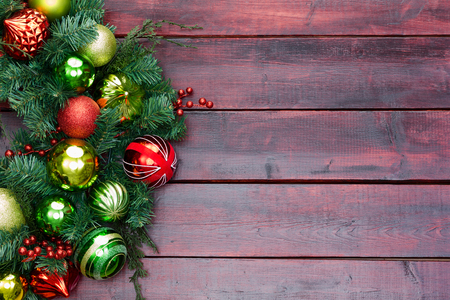 Red and green themed Christmas wreath on mahogany stained wood with woodgrain texture and copy space for your holiday wishes Imagens
