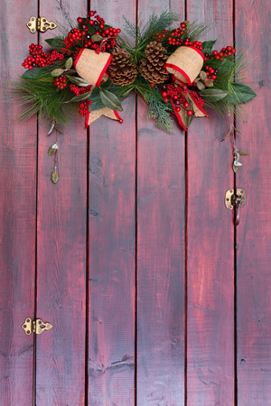 Simple elegant country Christmas decoration with burlap ribbon on mahogany stained wood of a barn door on a farm with copy space below for your holiday greeting