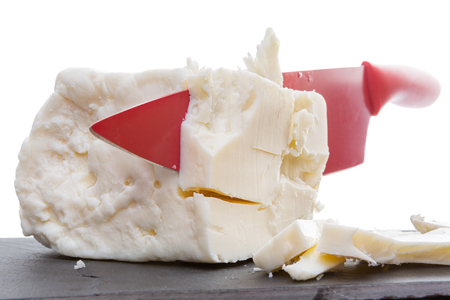 crumbly: Red ceramic knife slicing through full cream feta cheese made with cow milk in a close up view of the crumbly creamy texture